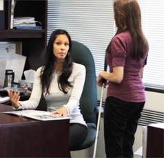 a visually impaired woman talking to another woman in an office