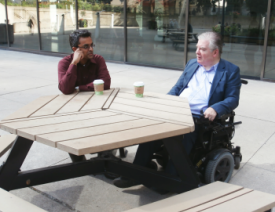 man sitting in a wheelchair at an outdoor table