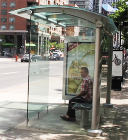 a bus shelter with someone sitting down inside of it