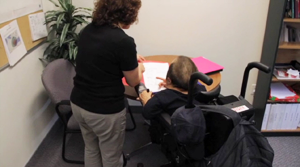 A woman and a man in a wheelchair discuss a document